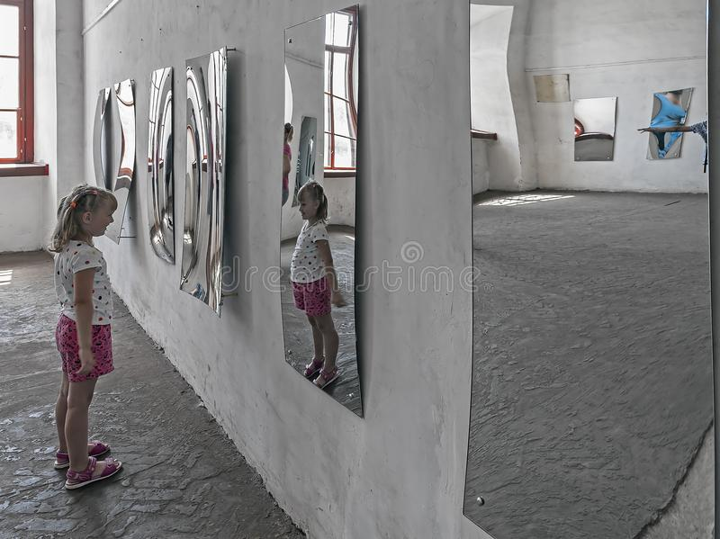 A girl looking at her image in the distorted mirror in the hall of mirrors royalty free stock images