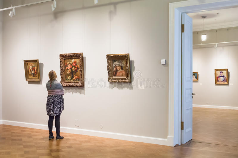 The girl is looking at Impressionist paintings Auguste Renoir stock image