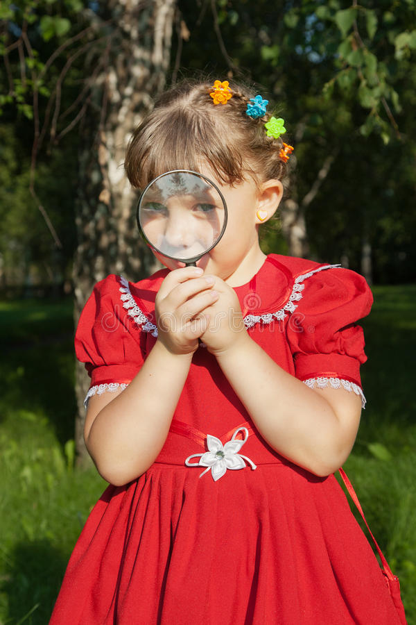 Girl looking through magnifiying glass at grass stock images