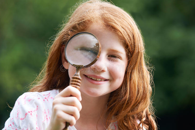 Girl Looking Through Magnifying Glass With Magnified Eye. Girl Looks Through Magnifying Glass With Magnified Eye royalty free stock image