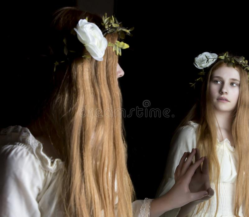 Girl looking in mirror. Girl with flower in hair looking in mirror stock photo