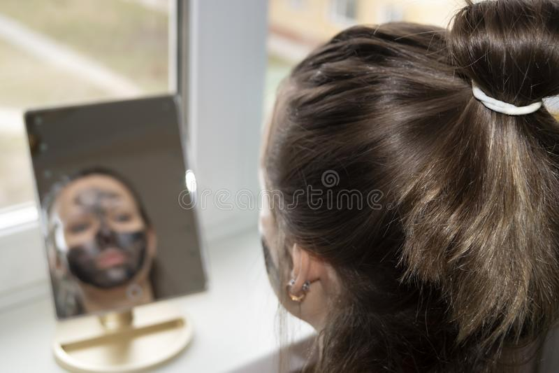 The girl looking in the mirror put a black mask. On her face stock image