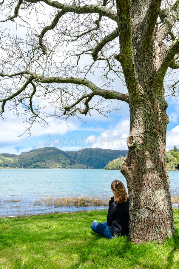 Girl looking over Sete Cidades lake into the mountains, Azores, Portugal. Girl looking at mountain scenery over Sete Cidades lake in spring time in Azores royalty free stock photos