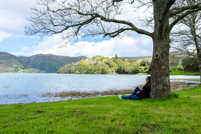 Girl looking over Sete Cidades lake into the mountains, Azores, Portugal. Girl looking at mountain scenery over Sete Cidades lake in spring time in Azores royalty free stock images
