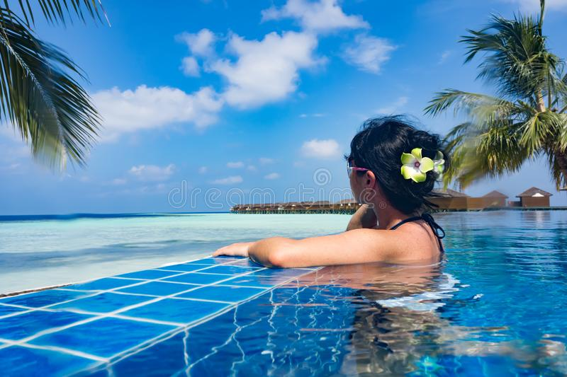 Girl looking at the ocean while sitting by the pool royalty free stock photo