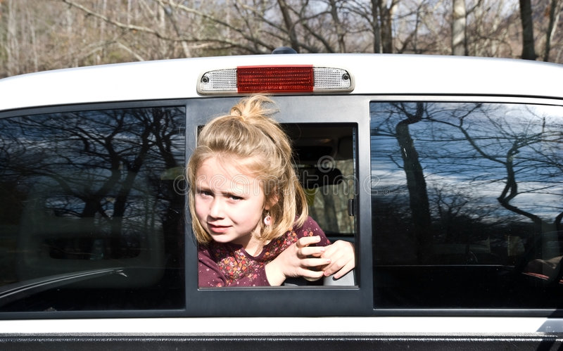 Girl Looking Out of Truck. A young girl looking out of the rear window of a truck. The landscape is reflected in the glass stock photography