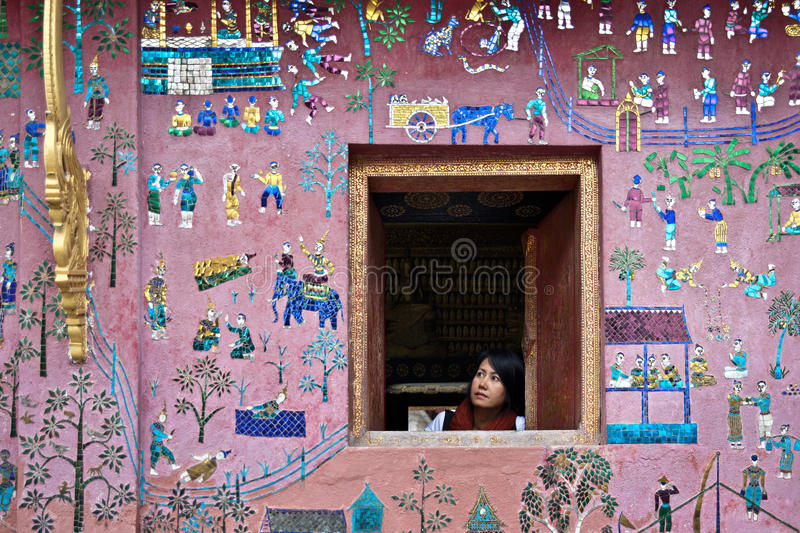 Girl looking out of the window with beautiful wall stock image