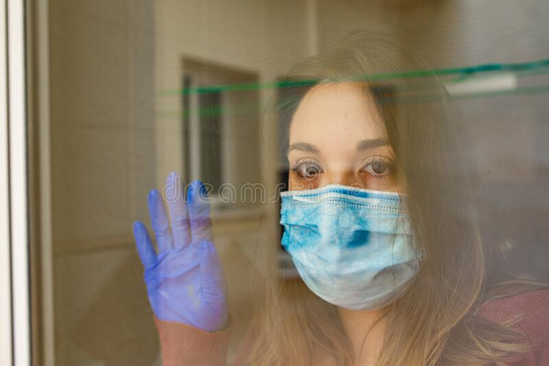 Girl looking out the window with face mask royalty free stock photos
