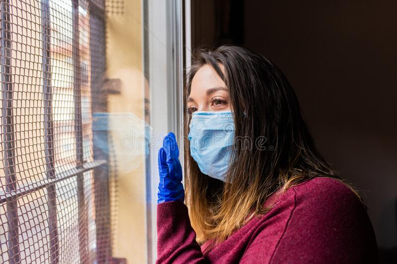 Girl looking out the window with face mask royalty free stock image