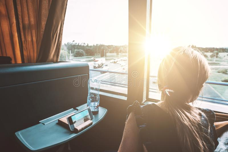 Girl Looking Out Window Reading Bus Sunset Landscape Peaceful Single royalty free stock images