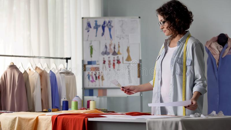 Girl looking at outline of new clothes collection, young designer, creativity. Stock photo royalty free stock images