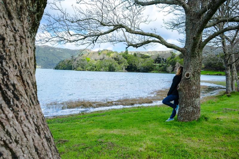 Girl looking over Sete Cidades lake into the mountains, Azores, Portugal. Girl looking at mountain scenery over Sete Cidades lake in spring time in Azores stock photos
