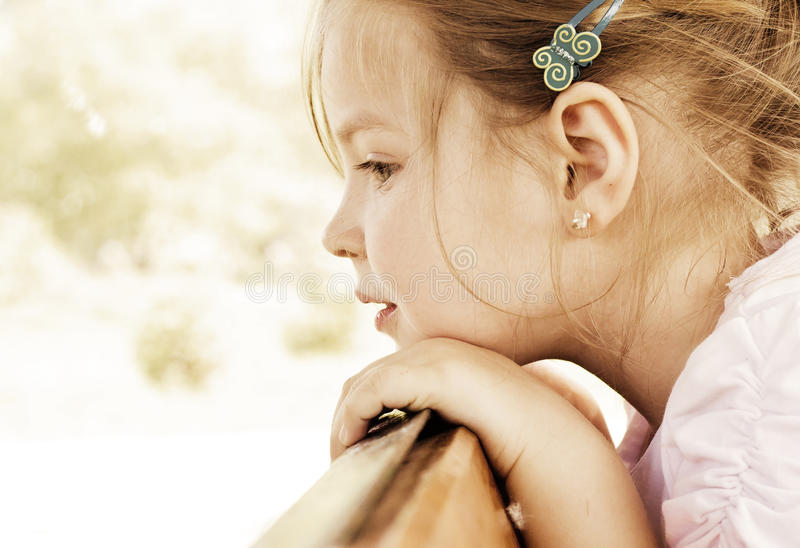 Girl looking over. A young girl looking over a fence or a barrier stock photo