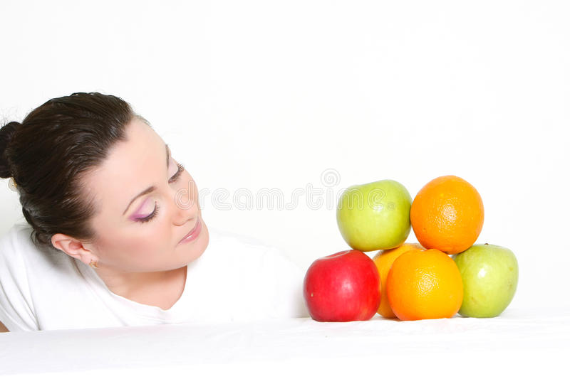 Girl looking at pile of fruits stock photo