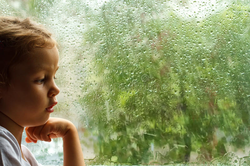 Girl looking at raindrops on the window stock images