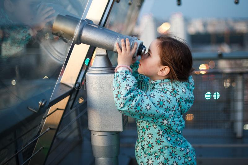 A girl is looking through a telescope stock images