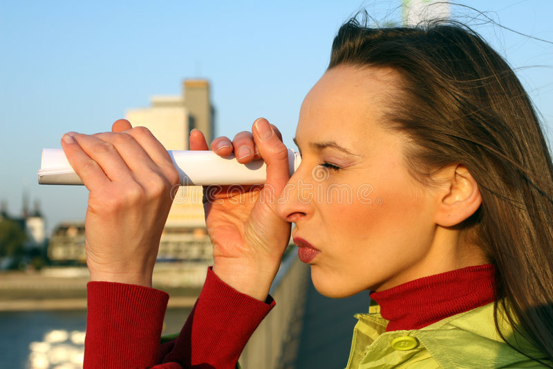 Girl looking through telescope stock photography