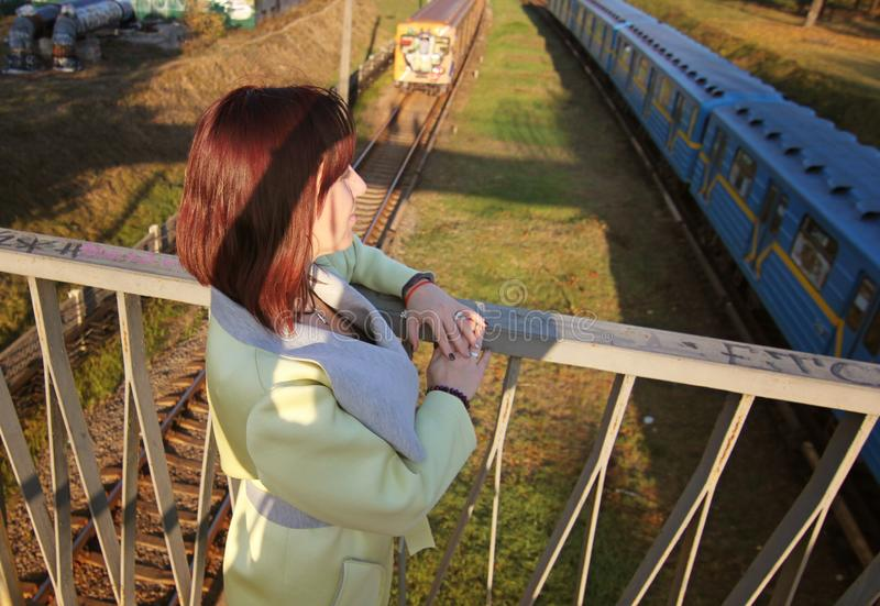 Girl looking at the train, which crosses a bridge. Young beautiful girl walking near railway tracks where the trains run royalty free stock images