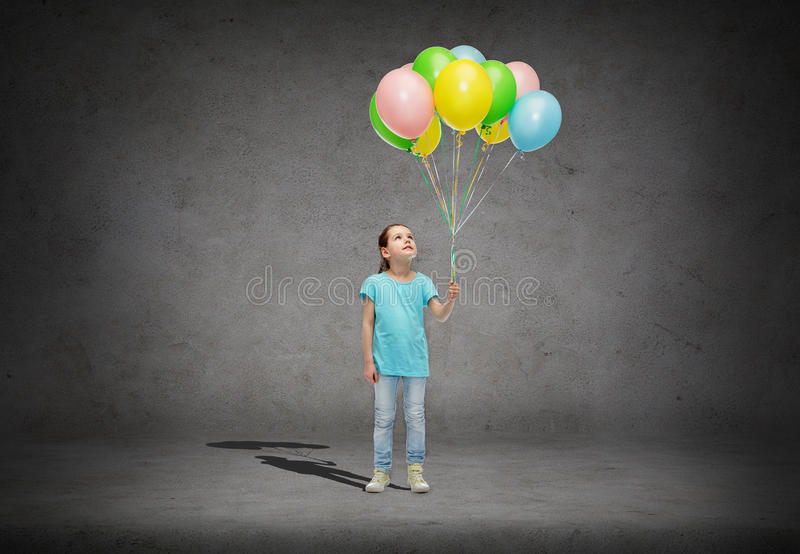 Girl looking up with bunch of helium balloons. Childhood, fashion, imagination and people concept - happy little girl looking up and holding bunch of colorful royalty free stock images