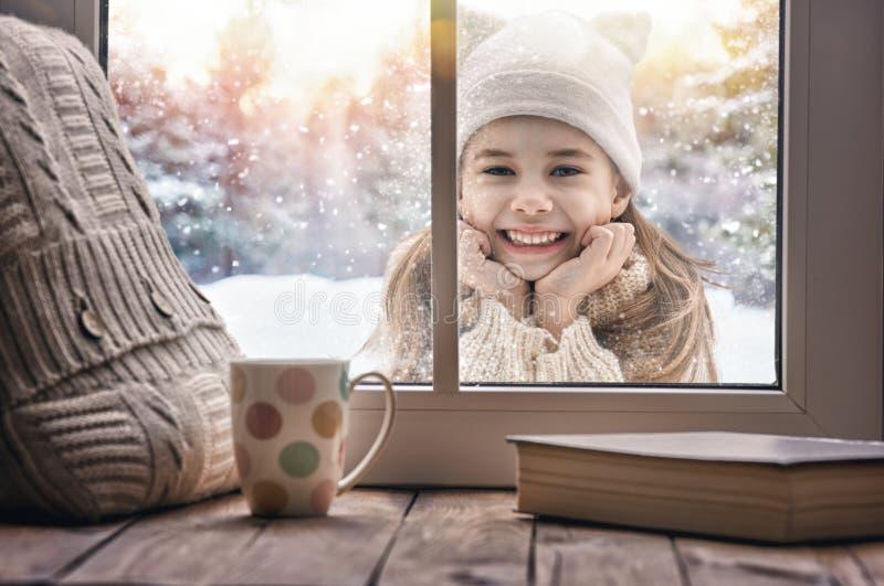 Girl looking in window stock photos