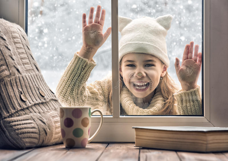Girl looking in window stock photography