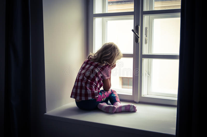 Girl looking through window royalty free stock photography