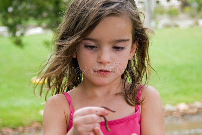 Girl Looking at a Worm stock images