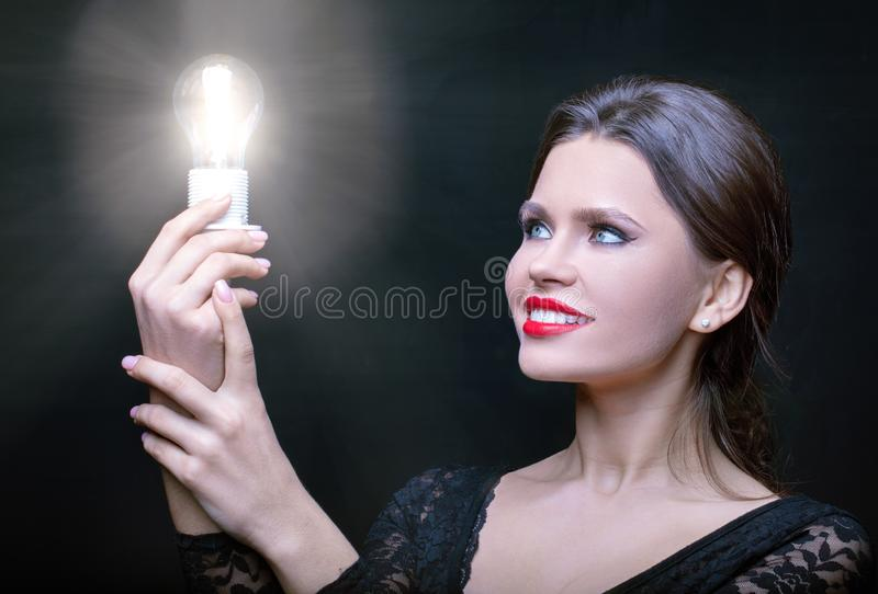 Girl looks with admiration at the burning bulb. Girl looks with admiration at the burning light bulb. In a dark Studio, a bright glowing bulb in the hands of the stock photography
