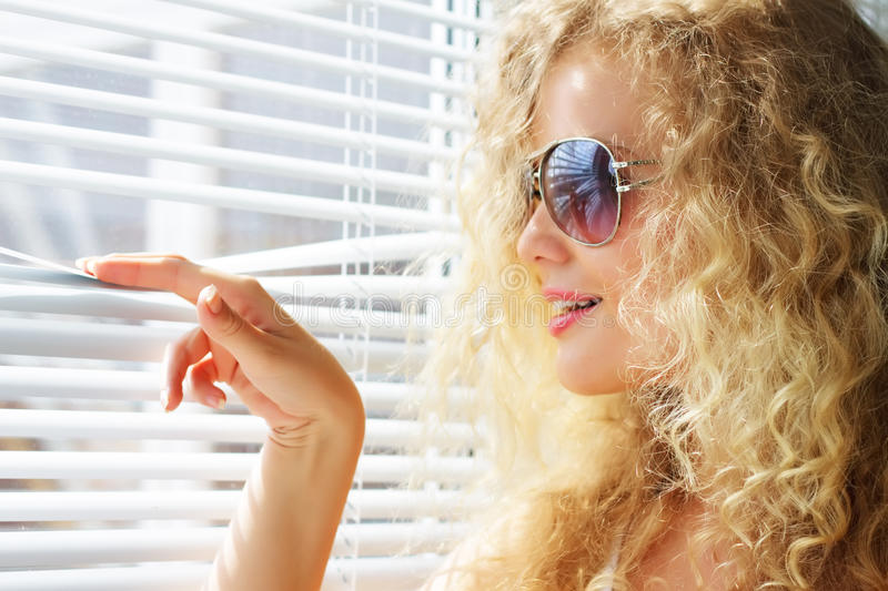 Download Girl Looks Through The Blinds Stock Photo - Image: 15192590