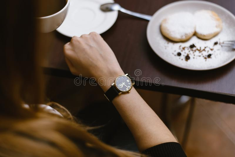 Girl looks at the clock in a cafe over a cup of coffee. time on the clock - the time for breakfast, dessert stock image