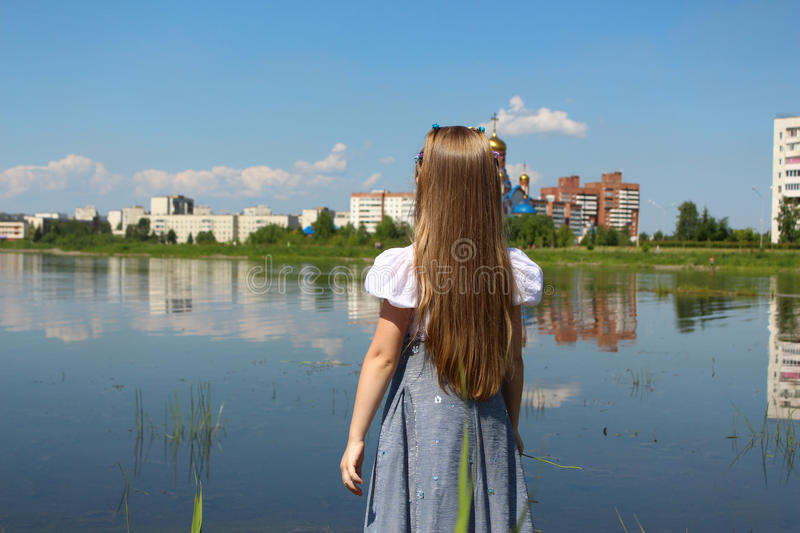 The girl looks into the distance at the lake stock photo
