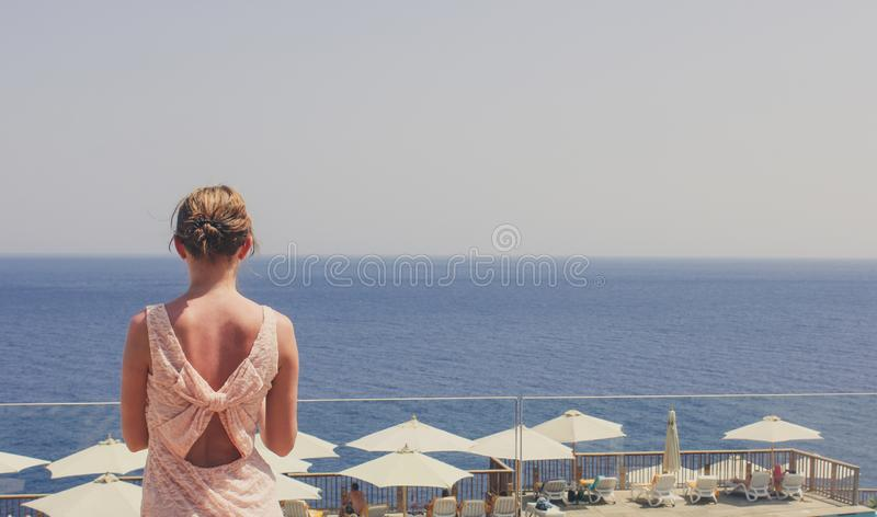The girl looks into the distance on the sea on a warm summer day stock images