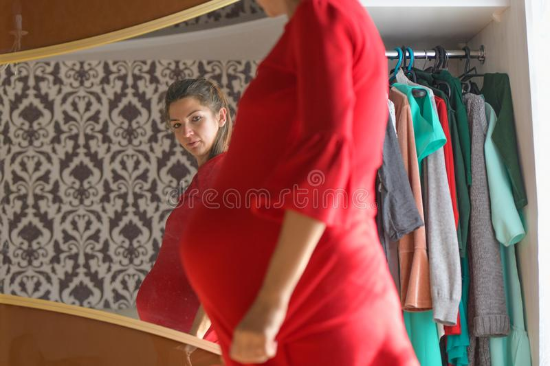 Girl looks at her pregnant belly. Close-up of a cute charming young European pregnant woman in a tight-fitting red dress holding stock image