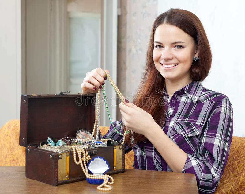 Girl looks jewelry in treasure chest stock photography