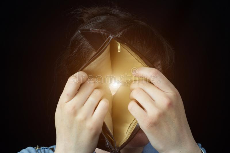 A girl looks through a leaky wallet, close-up, poorness royalty free stock photos