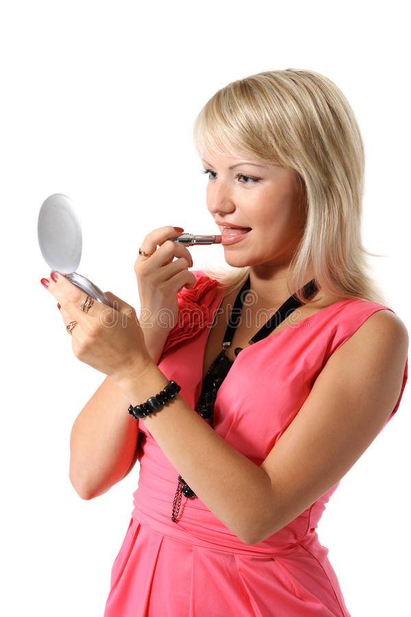 Girl looks into the mirror and lipstick stock image