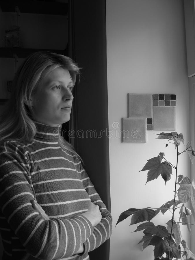 The girl looks out the window. Black-and-white photograph. The girl looks out the window.Black-and-white photograph royalty free stock image
