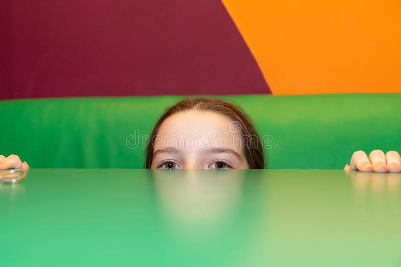 The girl looks from the table. In the cafe. Only the eyes and fingers are visible. The child was hiding. The background colors are bright orange, burgundy stock photography