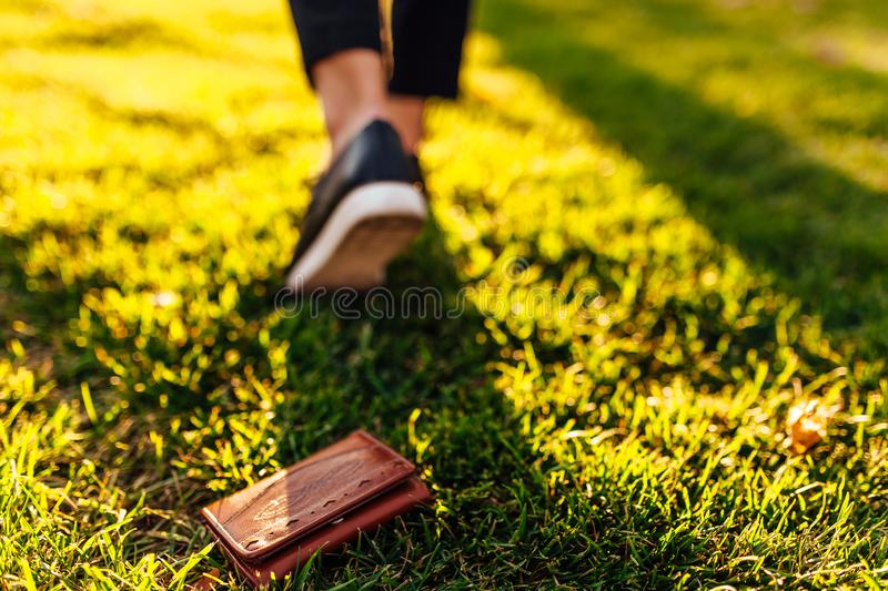 The girl lost a leather wallet with money on the street. Close-up of a purse lying on the grass and legs of a departing girl. The girl lost a leather wallet with stock photo