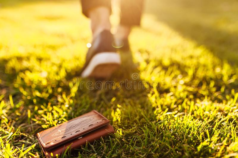 The girl lost a leather wallet with money on the street. Close-up of a purse lying on the grass and legs of a departing girl. The girl lost a leather wallet with royalty free stock photo