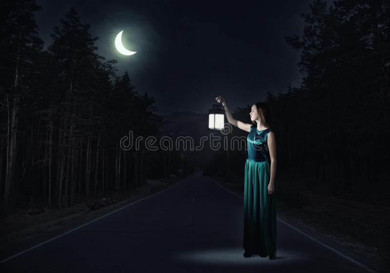 Girl lost in night. Young attractive woman in green dress with lantern walking in darkness royalty free stock images