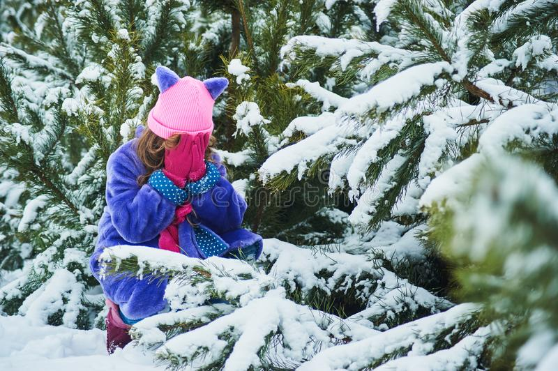 Girl lost in winter forest. lost in the woods and has a frightened face. Child crying in the forest stock photo