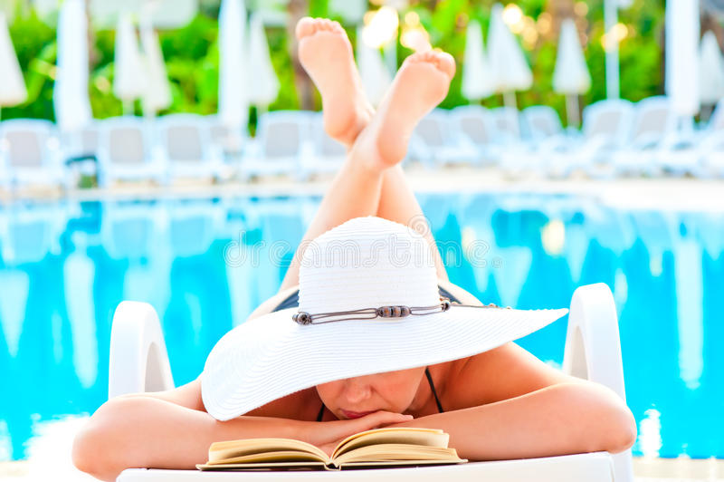 Girl in a lounge chair near the pool and reading a romance novel stock images