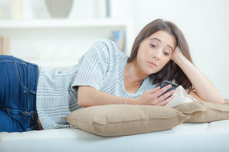 Girl lounging with cellphone. Applications royalty free stock photo