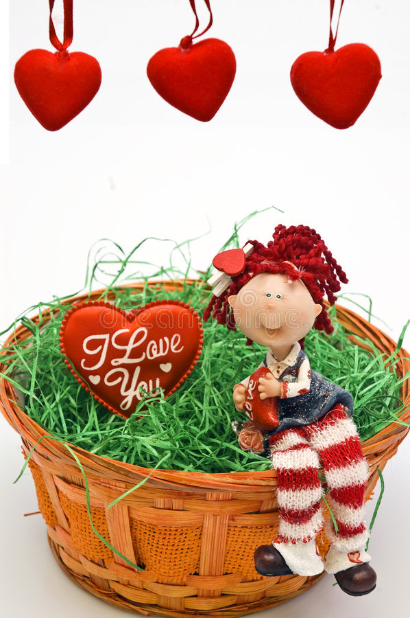 Girl in love. Figurine girl in love sitting in a basket with grass stock photo