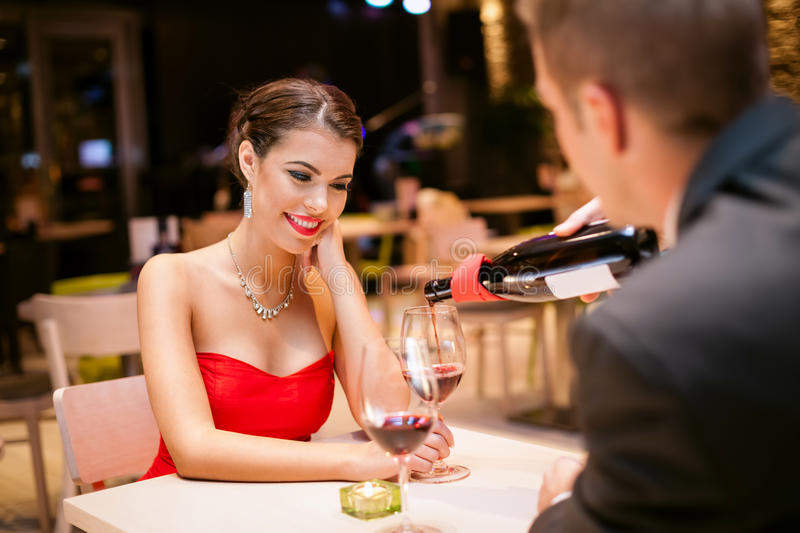 Girl in love with boyfriends. Beautiful girl with boyfriends in restaurant, he pouring wine in her glass stock images