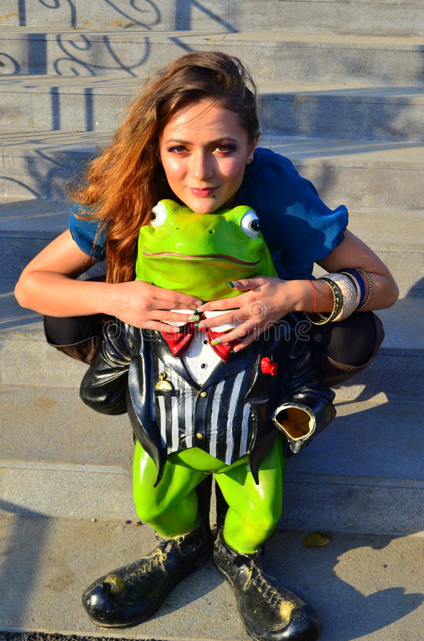 Girl in love with a frog stock image