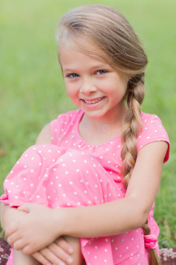 Girl with a lovely smile sitting on grass royalty free stock photos