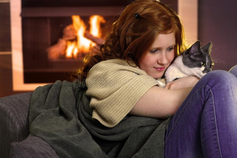 Girl loving cat at home. Red hair teenager girl fondling cat at home sitting by fireplace royalty free stock photography