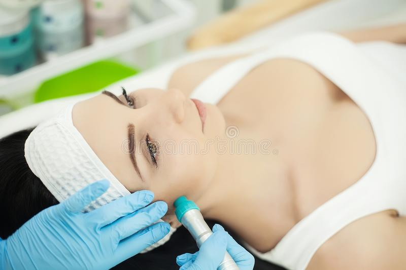 Girl lying in beauty spa enjoying skin therapy using current treatment royalty free stock photography